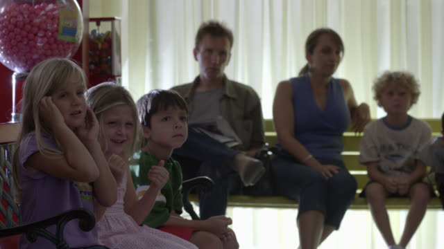 wide angle of children, seated on benches with parents or adults in waiting room, covering their faces and screaming. could be with fear or laughter. could be doctor or pediatrician's office. - weitwinkel stock-videos und b-roll-filmmaterial