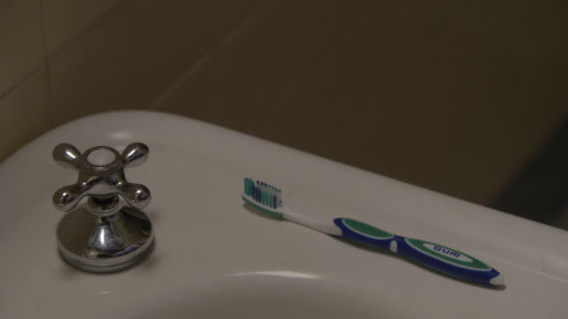 CLOSE ANGLE OF TOOTHBRUSH LYING ON PORCELAIN BATHROOM SINK.