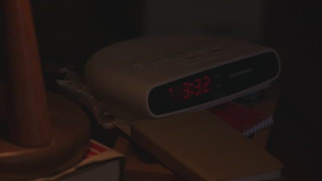 """close angle of alarm clock on cluttered nightstand with light on. clock radio reads """"3:32,"""" sits on books, note pad. could be pov of person unable to sleep. matching shot with 2209-023 clocks. - alarm clock stock videos & royalty-free footage"""