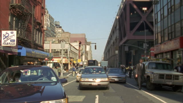 stockvideo's en b-roll-footage met back plate. traffic following camera. three lane one way street. buildings on either side of street. - 1992