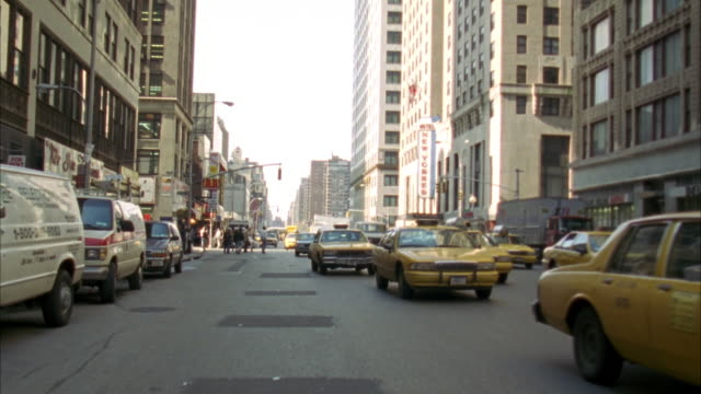 back plate. traffic following camera. see many taxi cabs driving along new york street. two lane one way street. buildings on either side of street. passes through intersection . traffic stops behind it. - anno 1994 video stock e b–roll