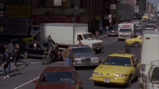 LOOKING DOWN ON FOUR WAY INTERSECTION. TRAFFIC PASSING FROM L-R IN BG. SILVER LINCOLN STOPPED BEHIND YELLOW TAXI AND RED CAR. SHOT ZOOMS IN ON WOMAN IN PURPLE JACKET STANDS UP OUT OF SUN ROOF AND LOOKS AROUND.