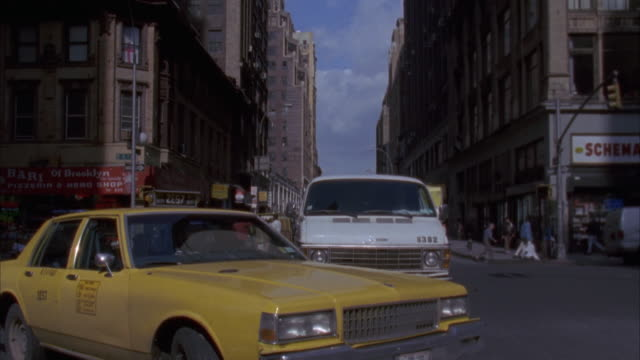 looking back at yellow cab about to turn right. buildings on either side of street. white van in bg. - 1992 stock-videos und b-roll-filmmaterial