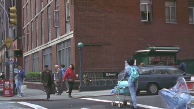 street corner with brick building in bg. subway entrance on side of building. pedestrians walking in bg and fg. woman in purple jacket runs in from behind camera. crosses street and goes down subway entrance. - 1994 stock videos and b-roll footage