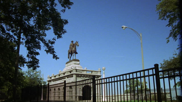 PULL BACK FROM BRONZE GRANT MEMORIAL STATUE OF MAN SITTING ON A HORSE IN LINCOLN PARK. STATUE ELEVATED ON WHITE STONE BASE. BLACK METAL FENCE AND TREE IN FG. PARK.