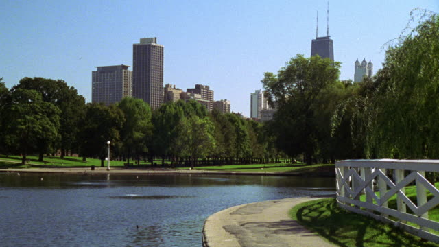 vídeos de stock, filmes e b-roll de zoom in from pond in a park to the john hancock center and high rise office buildings in bg. pond is surrounded by trees. skyscrapers. chicago skylines. multiple takes. could be lincoln park. - sony pictures entertainment