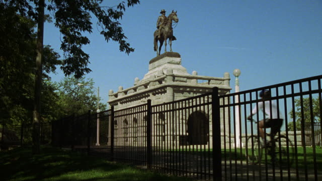 WIDE ANGLE OF BRONZE GRANT MEMORIAL STATUE OF MAN SITTING ON A HORSE IN LINCOLN PARK. STATUE ELEVATED ON WHITE STONE BASE. BLACK METAL FENCE IN FG. MAN ON BIKE RIDES PAST STATUE. PARK.