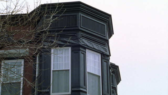stockvideo's en b-roll-footage met pan left to right of top floor windows in brick building. could be apartment building or office building. tree with bare branches in fg. multiple takes. - bare tree