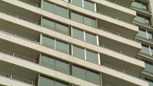 vídeos de stock, filmes e b-roll de pan up on upper class high rise apartment building or condominium building. trees with bare branches in fg. cars drive up to entrance of building. - sony pictures entertainment