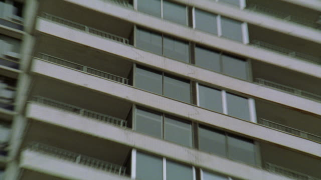 zoom in on windows of high rise upper class apartment building on condominium. - fensterfront stock-videos und b-roll-filmmaterial