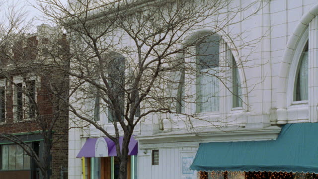 vídeos de stock, filmes e b-roll de medium angle of two story white building with green and purple awnings. could be shops in small town. trees with bare branches in fg. - sony pictures entertainment