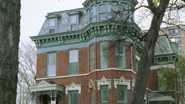 "ZOOM IN ON 4-STORY VICTORIAN-STYLE HOUSE. METAL FENCE AND STAIRS LEADING UP TO SECOND STORY. DEAD IVY ON SIDE OF HOUSE. LOWER CLASS. SWING SET IN FRONT YARD. MULTI-STORY BRICK BUILDING IN BG.<P><A HREF=""HTTPS://WWW.SONYPICTURESSTOCKFOOTAGE.COM/FOOTAGE?KID"