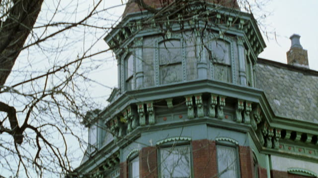pan down from domed roof of brick victorian-style house to window on lower story. tree with bare branches in fg. - 19th century style stock videos & royalty-free footage