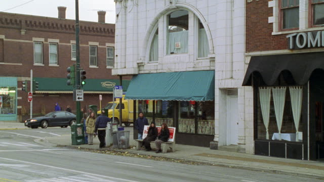zoom in on street corner. people sitting at bus stop. restaurant with green overhang or awning in bg. pedestrians passing on sidewalk. snow. - awning stock videos & royalty-free footage