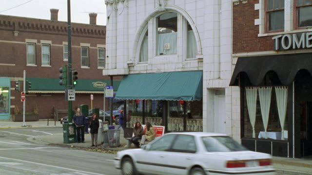 zoom in on street corner. people sitting at bus stop. restaurant with green overhang or awning in bg. pedestrians passing on sidewalk. snow. - 1996 stock videos & royalty-free footage