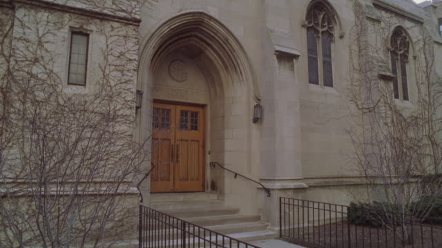 stockvideo's en b-roll-footage met zoom in from wide angle of entrance to church or chapel to upper floor window. could be convent, rectory, or chapel. winter. tree branches bare. could be catholic school. - bare tree