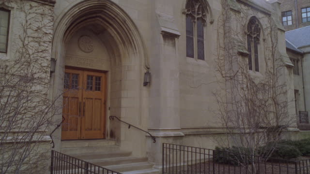 stockvideo's en b-roll-footage met medium angle of entrance to church or chapel. could be convent, rectory, or chapel. winter. tree branches bare. could be catholic school. winter. - bare tree