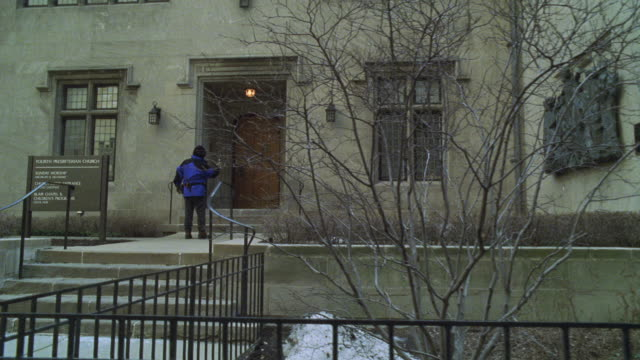 vídeos de stock, filmes e b-roll de zoom in to entrance of concrete apartment building. man in blue jacket walks up stairs to door as another man comes out. they converse. trees bare and snow on ground. - sony pictures entertainment