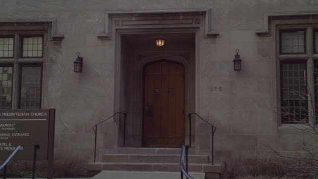 vídeos de stock, filmes e b-roll de medium angle of entrance to gray, brick church. wooden door. could be rectory or convent. tree branches bare. - sony pictures entertainment