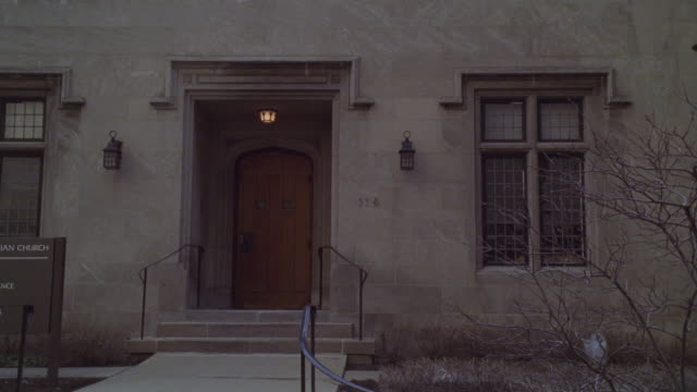 stockvideo's en b-roll-footage met zoom in on entrance to gray, brick church. wooden door. could be rectory or convent. tree branches bare. - bare tree