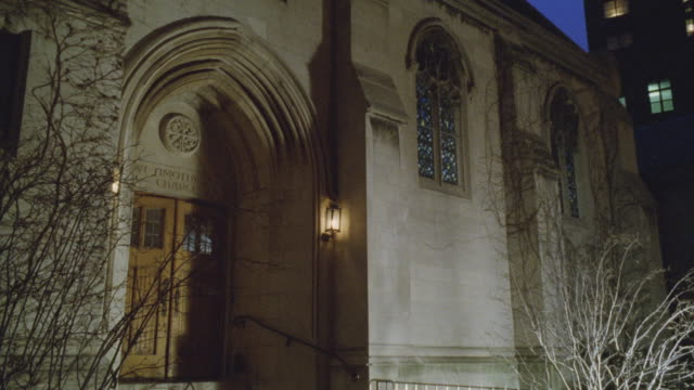 meidum angle of entrance to church, chapel, or cathedral. arched doorway. bare trees. winter. stained glass windows. - chapel stock videos & royalty-free footage