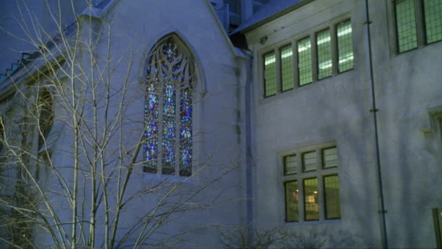 medium angle of stained glass window in church or chapel. could be catholic school. tree with bare branches. - illinois stock videos and b-roll footage