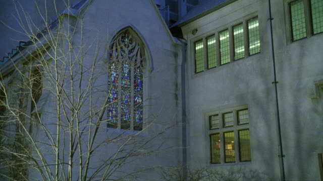 stockvideo's en b-roll-footage met medium angle of stained glass window in church or chapel. could be catholic school. tree with bare branches. - bare tree