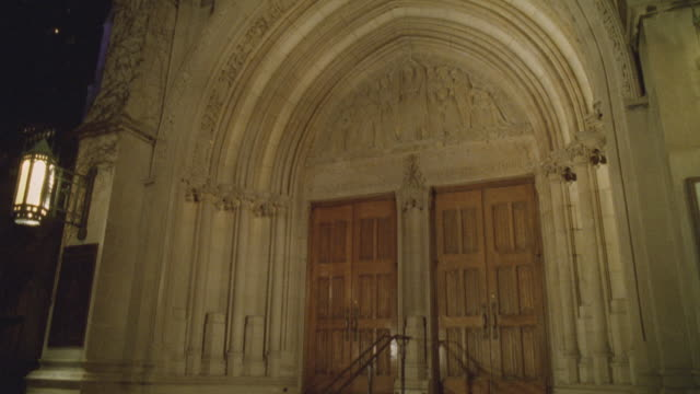 up angle of spire of church or catherdral. camera pans down to entrance to church. religious art scultpure or relief above doorway. arched doorway. - spire stock videos & royalty-free footage