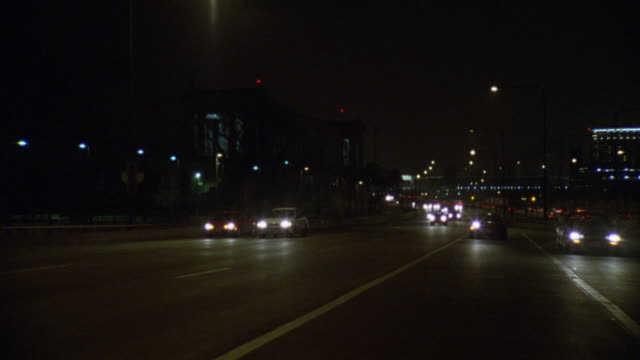vídeos de stock, filmes e b-roll de tracking shot from front of cars driving on freeway or highway. traffic. downtown chicago skyline visible in bg. cities. overpasses. - placa de processo
