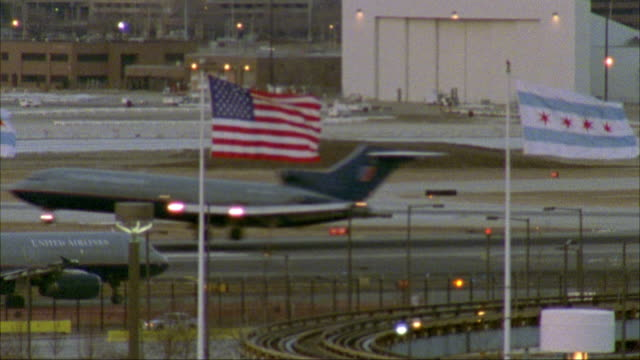 stockvideo's en b-roll-footage met view of runway of chicago o'hare airport with airplane landing r-l. american flag and chicago city flag waving on two flag poles and  el-train tracks in fg. - nationale vlag