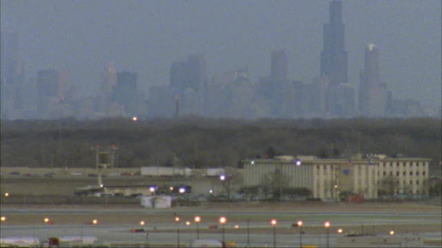 wide angle of airplane landing from l-r with chicago skyline in bg. camera pans left to taxiing united commercial airliner, airplane, plane moving l-r. el-train traveling on tracks in fg. - 1996 video stock e b–roll