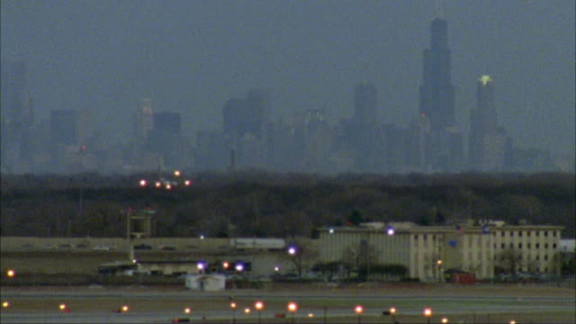 wide angle of commercial airliner descending for landing over runway of o'hare airport with chicago skyline in bg.  airplanes, planes, jets. - 1996 stock videos & royalty-free footage