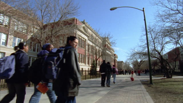 stockvideo's en b-roll-footage met wide angle of students, people walking on sidewalk in front of  three story brick and stone building. could be on college, university or high school campus. - school building