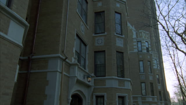 """pan down of middle or upper class, multi-story brick and stone apartment building. woman walking on sidewalk then enters building. residential area. neighborhood.<p><a href=""""https://www.sonypicturesstockfootage.com/footage?kid=4321"""">for day-night matching - upper class stock videos & royalty-free footage"""