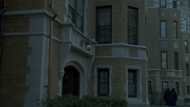 """pan down from second story window of middle or upper class, multi-story brick and stone apartment building. woman walking on sidewalk then enters building. residential area. neighborhood.<p><a href=""""https://www.sonypicturesstockfootage.com/footage?kid=432 - upper class stock videos & royalty-free footage"""