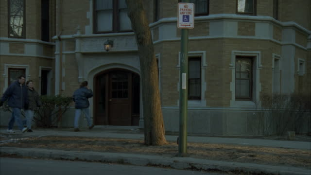 """pull back from front door of building to show middle or upper class, multi-story brick and stone apartment building with courtyard. people walking past building. residential area. neighborhood.<p><a href=""""https://www.sonypicturesstockfootage.com/footage?k - upper class stock videos & royalty-free footage"""