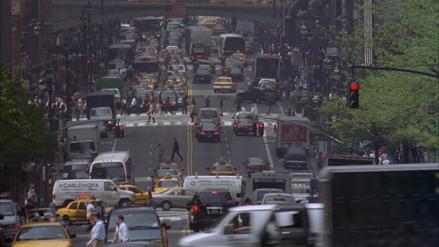 wide angle shot of major city street with high traffic flow.  many pedestrians cross the street.  city buses and taxis  fill the road. camera pans down to lower part of street.  pans back up to the bridge above the freeway. - major road stock-videos und b-roll-filmmaterial