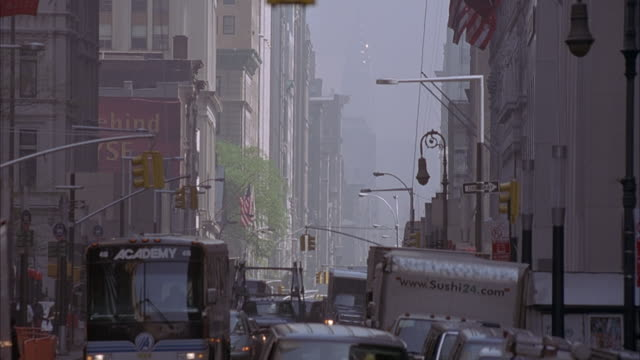 wide angle shot of major city street with large trucks driving on the road. camera pans down to the street level with bumper to bumper traffic visible. see pedestrians walking across crosswalk. could be lower manhattan. - major road stock-videos und b-roll-filmmaterial
