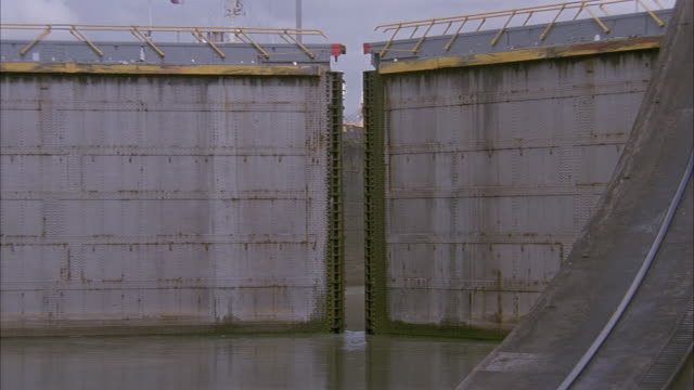 wide angle. ship waiting to enter lock in panama canal. doors in fg open for ship to come through. - パナマ運河点の映像素材/bロール