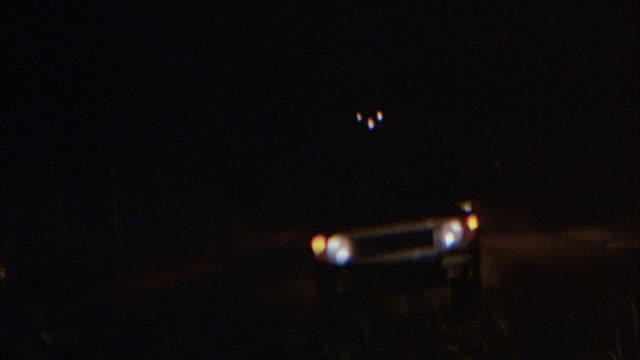 'medium angle driving down road behind other cars. see police cars and police men out in front directing traffic. shot pans up to rear view mirror, see suv following behind. pans down to front windshield. camera veers left, across other side of road, and - anno 2001 video stock e b–roll