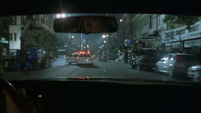 medium angle from pov of passenger seat inside car. following behind police car, chasing black convertible. police car in front spins out and hits car. camera veers right. see driver of car in shot. - パトカー点の映像素材/bロール
