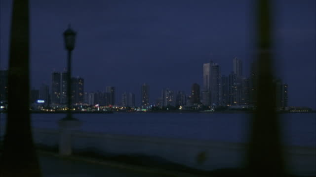 MEDIUM ANGLE. FRONT PLATE. CAMERA DRIVING DOWN HIGHWAY IN PANAMA. HIGHWAY RUNS ALONG COASTLINE. CAMERA PANS RIGHT TO PANAMA CITY SKYLINE IN BG. PANS BACK AND FORTH BETWEEN HIGHWAY AND SKYLINE.