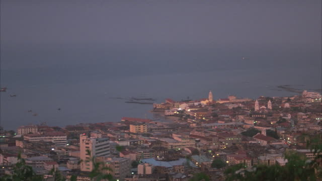 WIDE ANGLE OF PANAMA CITY. SEE HOUSES AND BUILDINGS ON SHORE SIDE. OCEAN IN BACKGROUND.