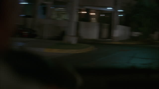 MEDIUM ANGLE DRIVING ON ROAD THROUGH PANAMA CITY. PASSENGER POV. STOPS BEHIND RED CAR THAT BEGINS TO REVERSE. CAMERA MOVES BACK AS WELL.