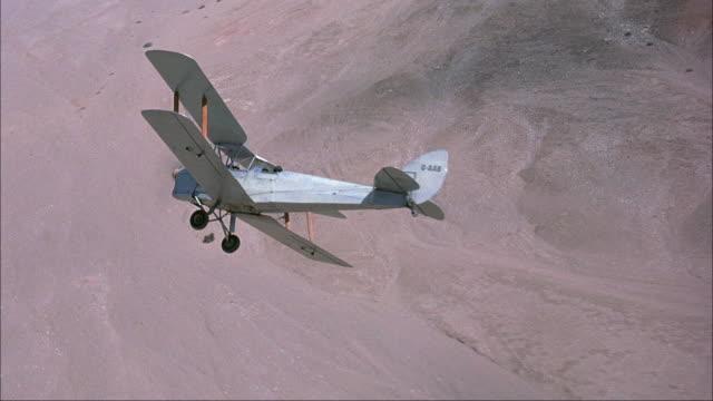 medium angle of small white propeller biplane flying over desert town. see plane bank right. - propeller video stock e b–roll