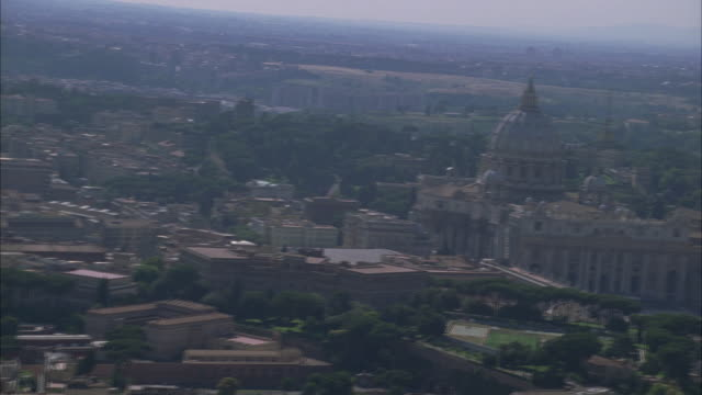 aerial of helicopter flying over city of rome. city streets visible. buildings and trees visible. st. peter's basilica visible. vatican city. - prato rasato video stock e b–roll