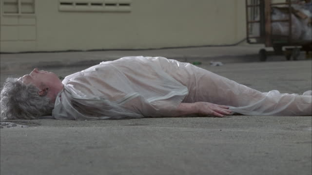 medium angle of corpse lying on ground in body bag. see black van drive away in background. silver cadillac cts drives from right and runs over corpse, who rolls to the right. death dead bodies. - cadillac stock videos & royalty-free footage