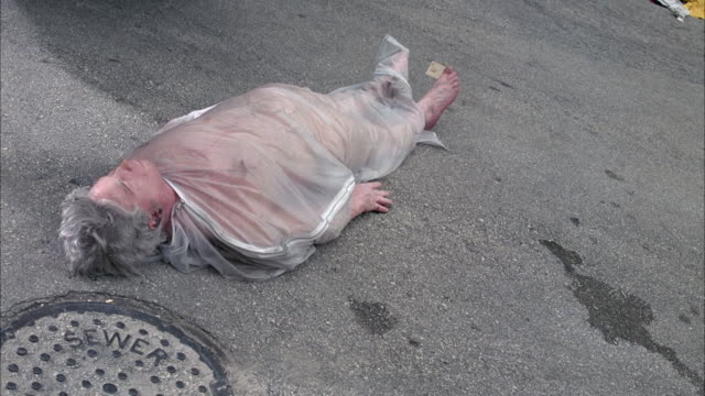 medium angle down of corpse lying on ground in body bag. silver car drives in from frame right and runs over the body. corpse rolls away. see pile of clothes on right in alley. death  dead body. - bag stock videos & royalty-free footage