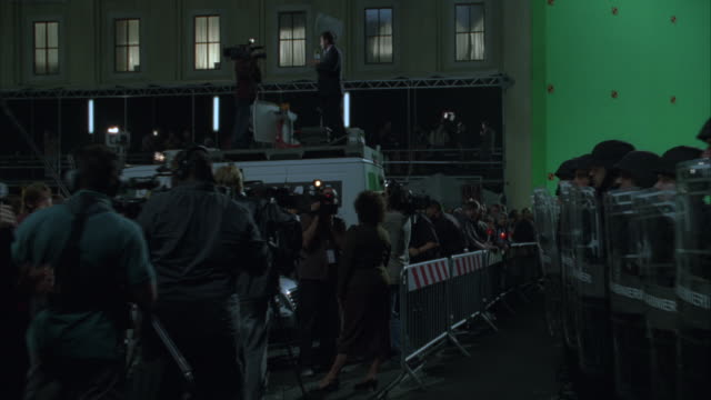 vídeos de stock e filmes b-roll de zoom in along barrier between swat team and reporters and crowd. crowd stands to left of frame with candles, signs, flags, and banners. reporters with microphones and cameras. swat team with shields to right of frame. green screen in bg. metal barricades - ponte de manhattan