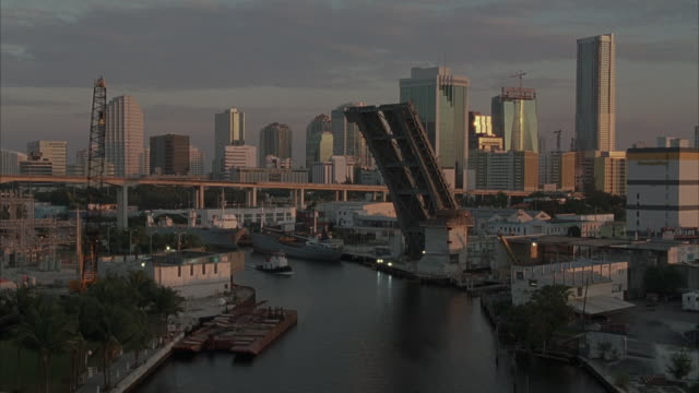 est wide angle of miami skyline at sunset in background. see tugboat traveling up canal in foreground. drawbridge is up. see monorail running from left to right in background. - drawbridge stock videos and b-roll footage